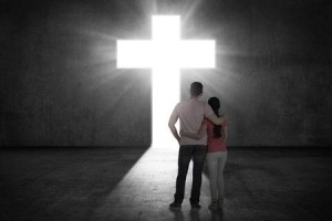 49598634-young-couple-looking-the-shining-cross-on-the-wall-religious-concept