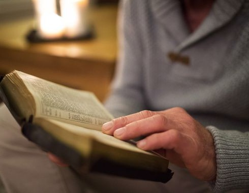 Unrecognizable man at home reading Bible, burning candles behind him